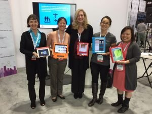 Five women standing holding iPads