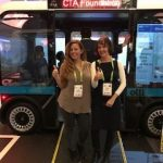 Two women stand in front of accessible olli bus