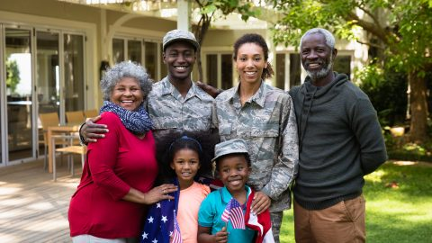 Portrait of a young adult African American male soldier and a young adult mixed race female soldier with thier diverse multi-generation family in the garden outside their home, embracing and smiling to camera, a US flag draped over the shoulders of the kids