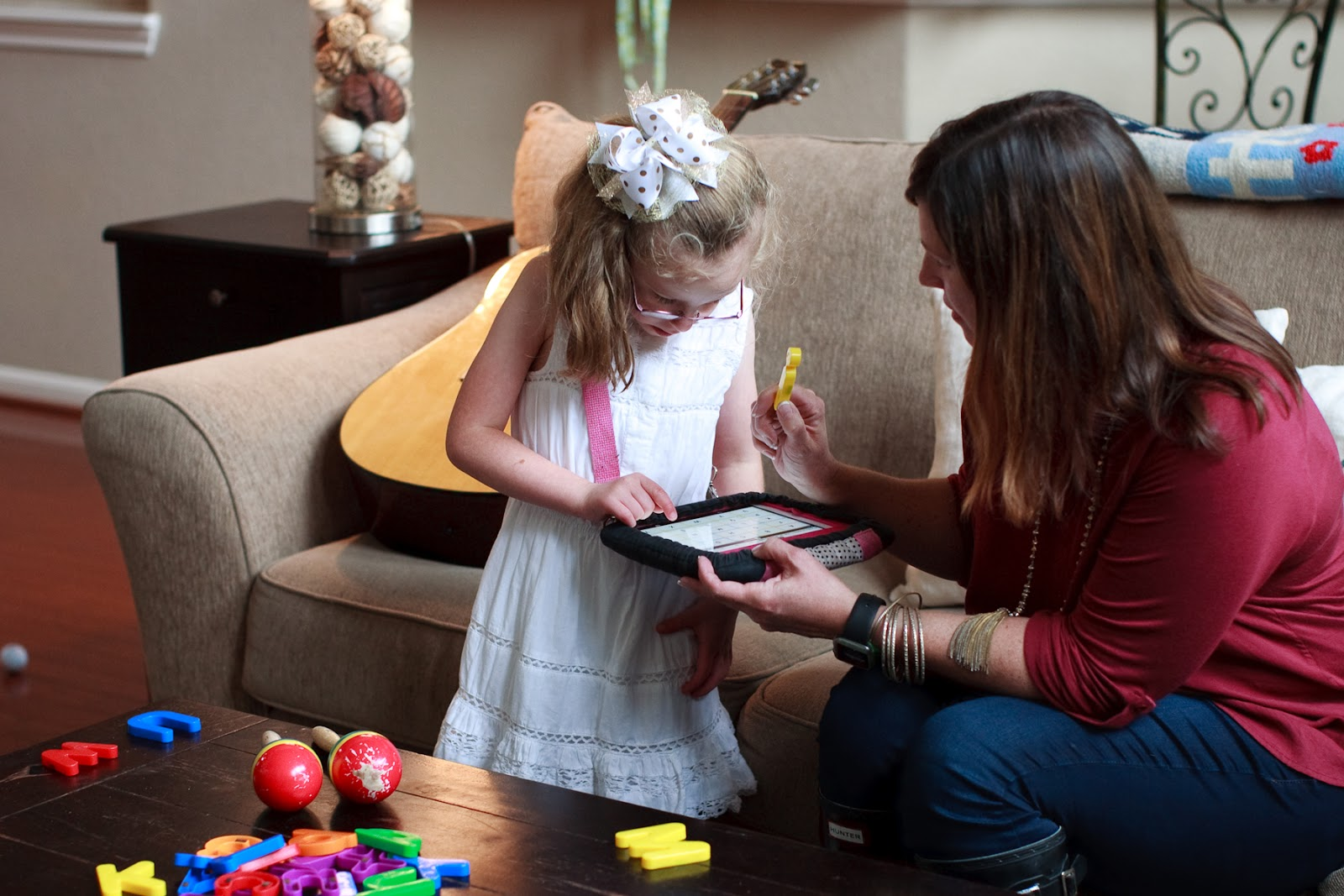 young girl using ipad with mom