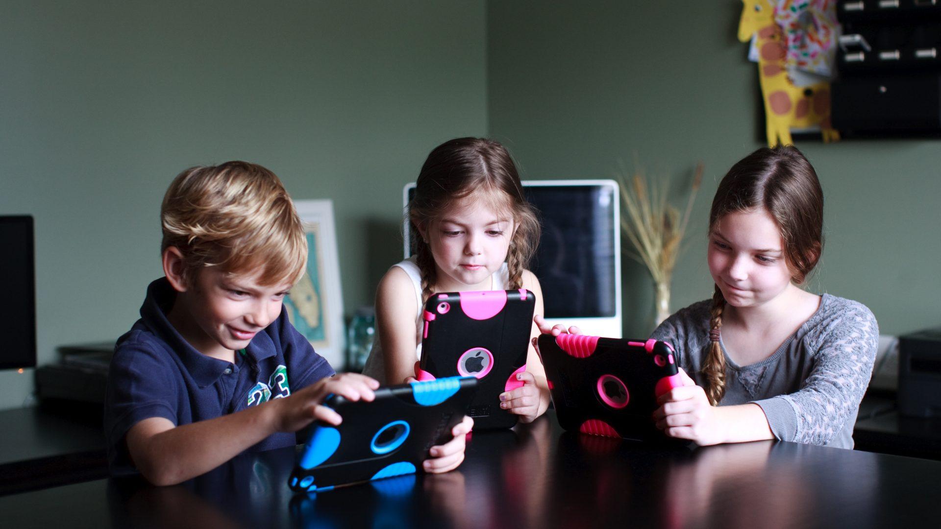 3 children using ipads