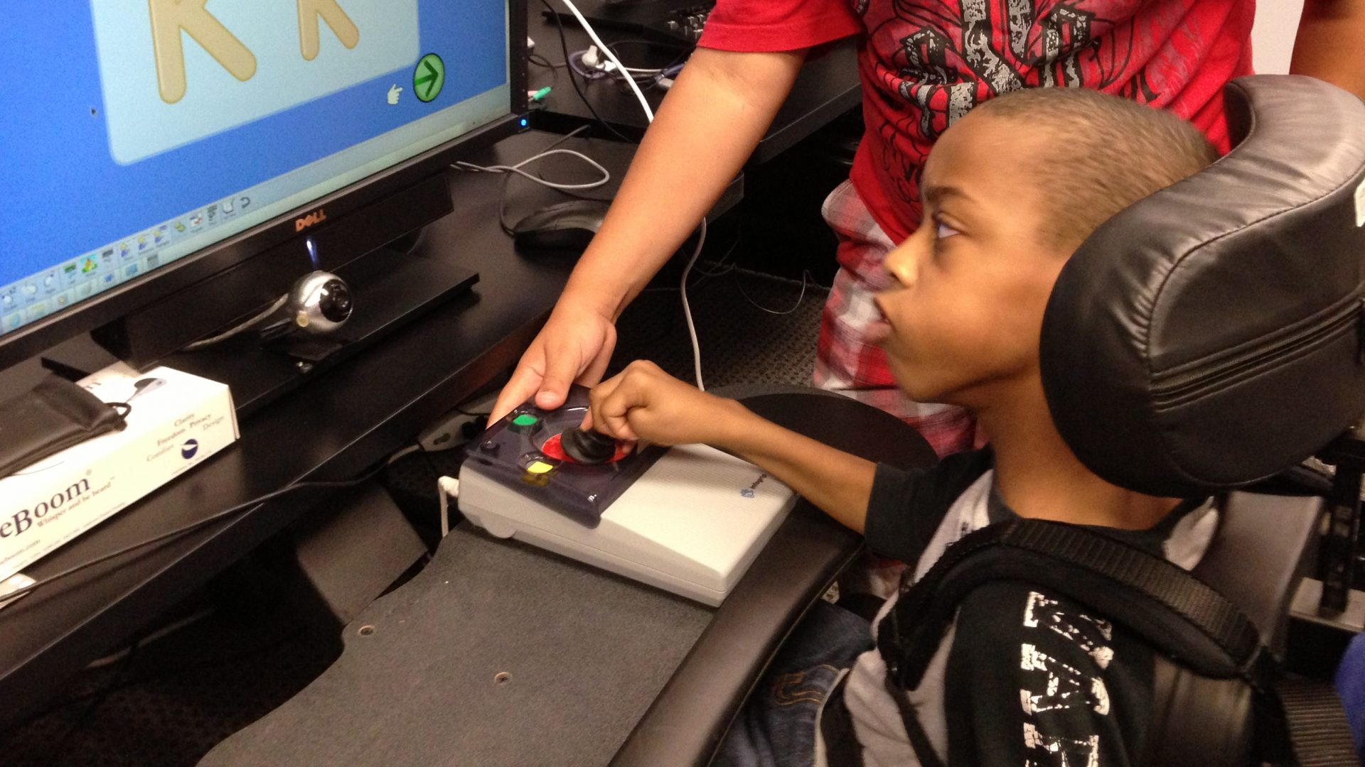 African American boy with Joystick Pro and computer monitor