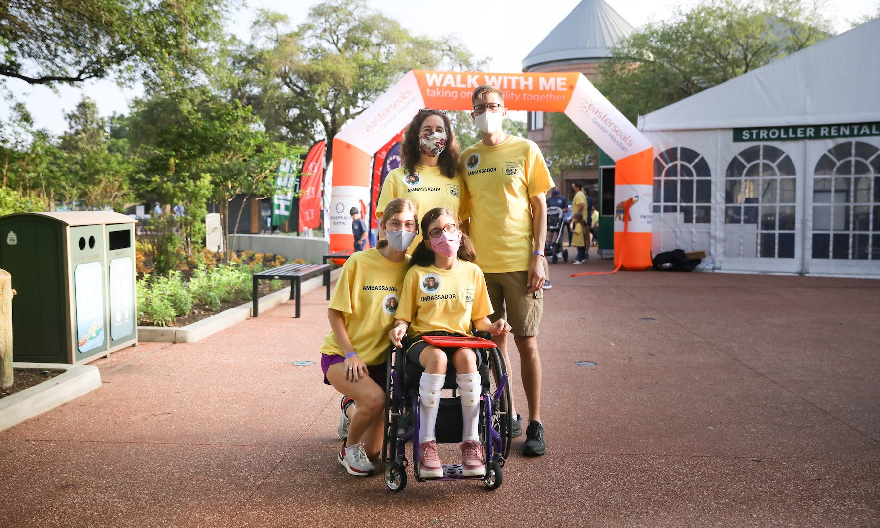girl with in wheelchair holding ipad with family
